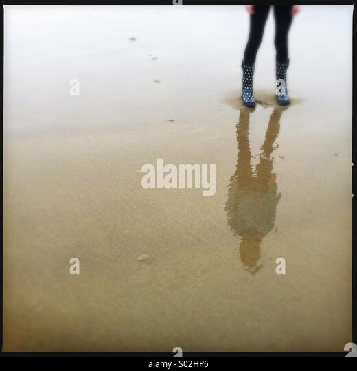 reflection of person standing on wet sand - Stock Image