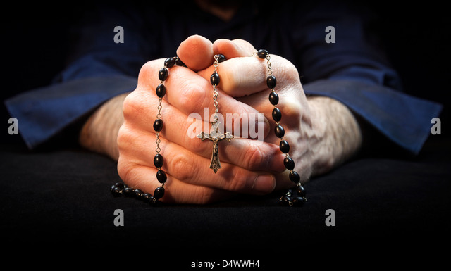 Hands holding rosary beads and cross while praying. - Stock Image