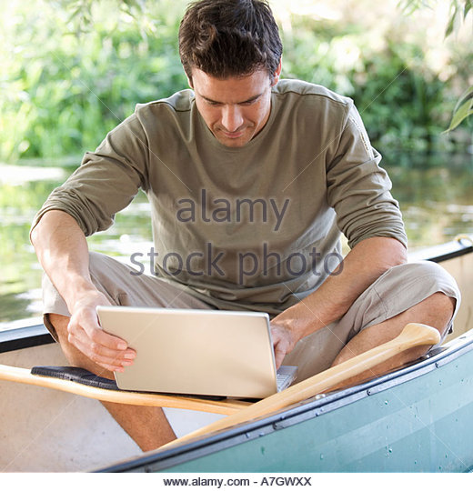 Young man sitting in a boat working on a laptop - Stock-Bilder