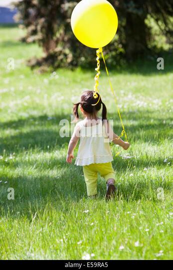 Girl carrying balloon in backyard - Stock Image