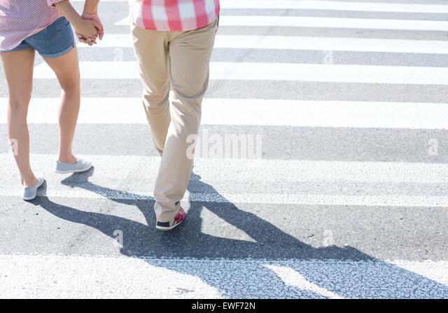 Low section of couple walking on crosswalk - Stock Image