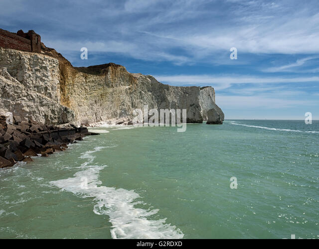 Crumbling chalk cliffs of the Sussex Downs tower above the beach at Seaford on the south coast of England, UK - Stock Image