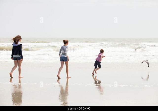 Family of 3 playing at beach - Stock Image