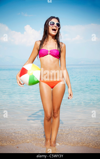 young female at the beach playing ball - Stock Image