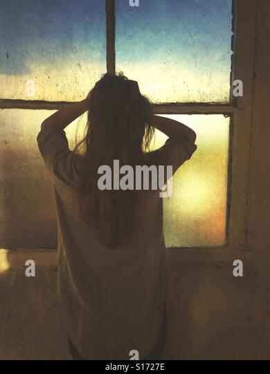Rear view of a stressed woman head in hands by the window - Stock-Bilder