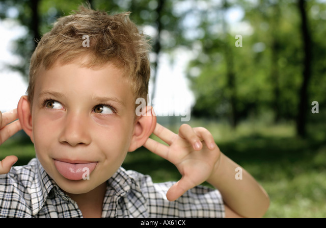 Boy making a grimace at camera - Stock Image