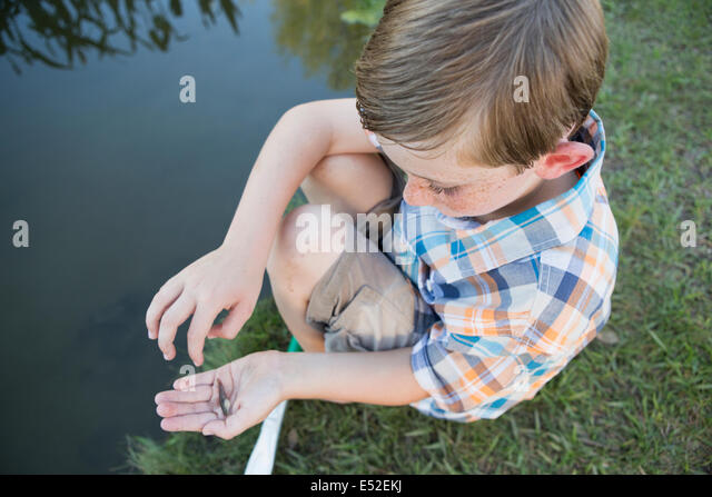 A young boy outdoors sitting on a riverbank with a small fish in the palm of his hand. - Stock Image