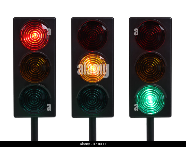 Three traffic lights with red yellow and green lights cut out on white background - Stock Image