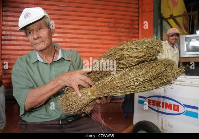 Managua Nicaragua Mercado Roberto Huembes market shopping Hispanic man elderly wrinkled bundled carry straw for - Stock Image
