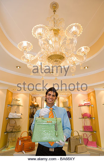Salesman displaying purse - Stock Image