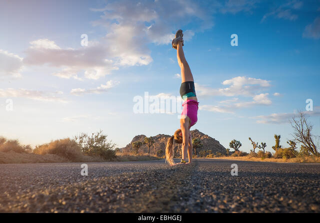 Woman doing hand-stand, Joshua Tree National Park, California, US - Stock Image