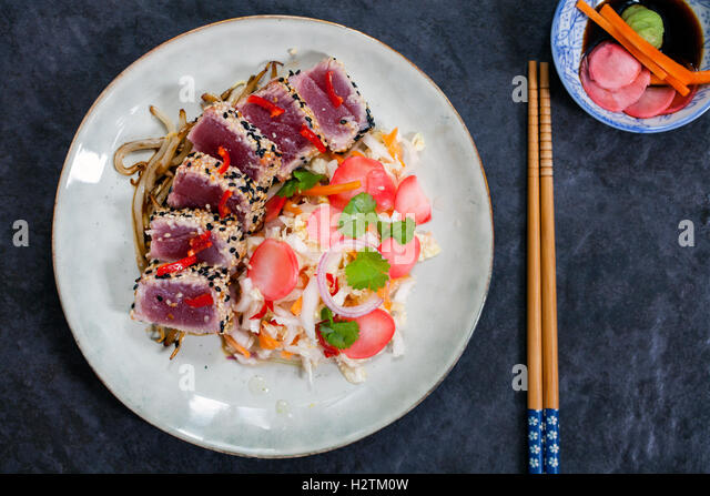 Sesame seeds crusted seared tuna with spicy asian salad and pickled radishes - Stock Image
