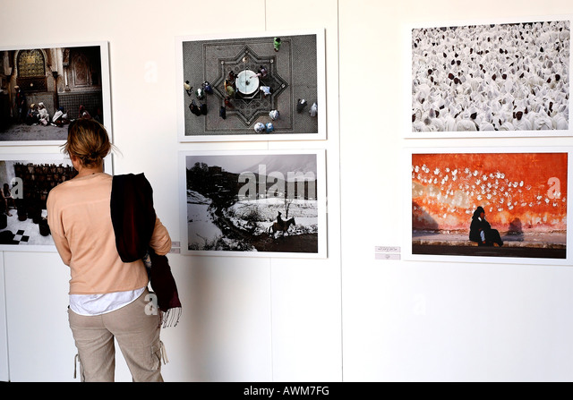 Female tourist looking at modern Moroccan photographs, exposition at Palais EL Badi, Marrakech, Morocco, Africa - Stock Image