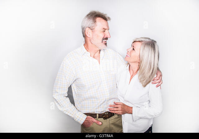 A mature couple posing in a studio arm in arm. - Stock-Bilder