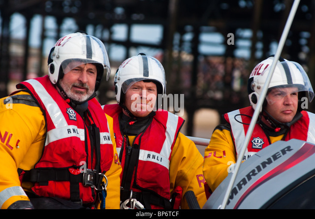 RNLI (Royal National Lifeboat Institution) personnel on manoeuvres at Blackpool beach, England. - Stock Image