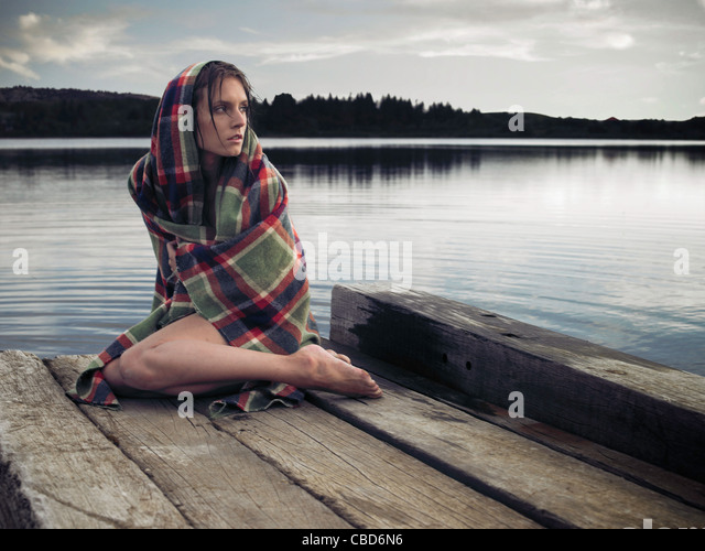 Woman in blanket on dock by lake - Stock Image