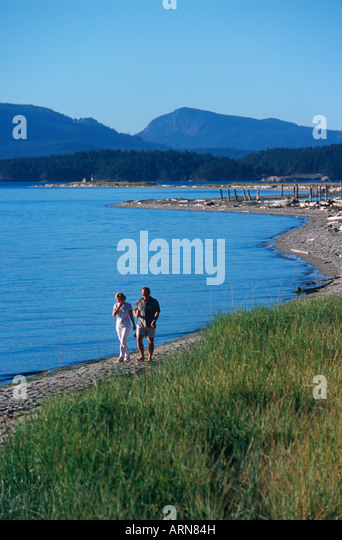 Sidney Spit , Gulf Islands National Park, people walk beach, British Columbia, Canada. - Stock Image
