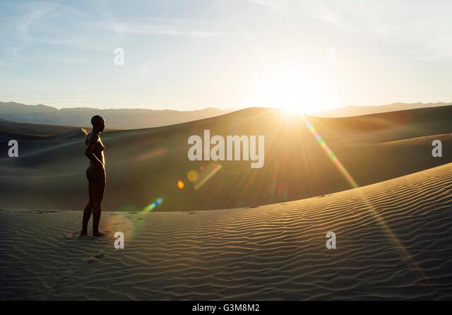 Nude woman in desert on sand dune looking away - Stock Image