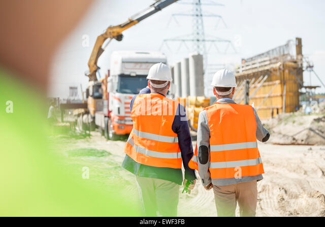 Rear view of supervisors walking at construction site - Stock-Bilder