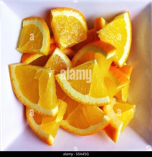 Quartered orange slices in white square bowl - Stock Image