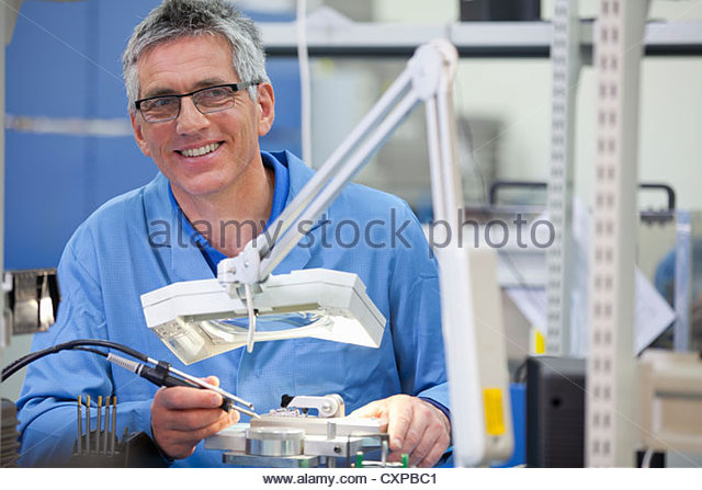 Portrait of smiling technician working on assembly line in hi-tech electronics manufacturing plant - Stock Image