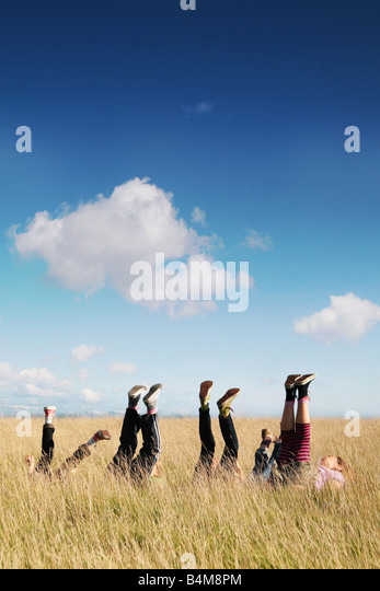 children lying in grass with legs in the air - Stock Image