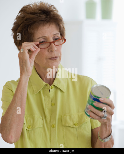 Senior woman reading label on food can - Stock Image