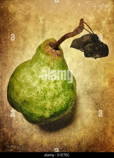 A pear with leaves against a textured background. - Stock-Bilder