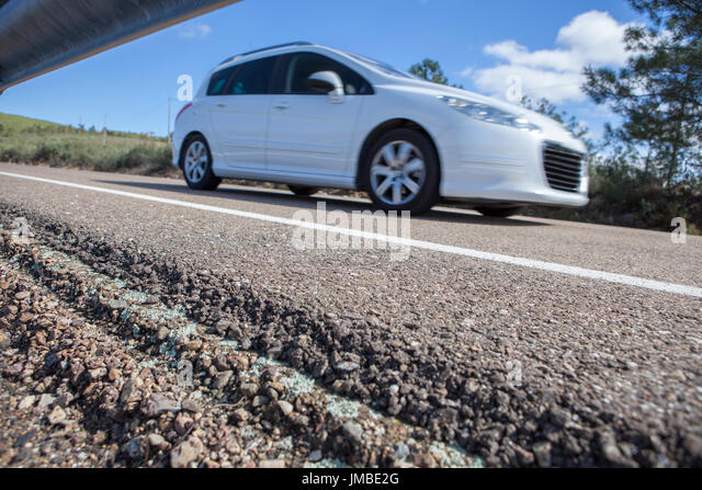 Station wagon car driving by country road. Motion blurred shot - Stock Image