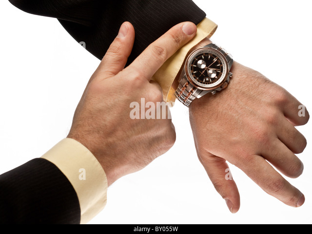 Man's hand in the suit pointing on his watch - Stock Image