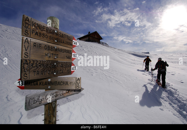 Sign post at Kniebergsattel or Knieberg Saddle, snowshoe hikers hiking to Alpe Nemes Mountain, High Puster Valley - Stock Image