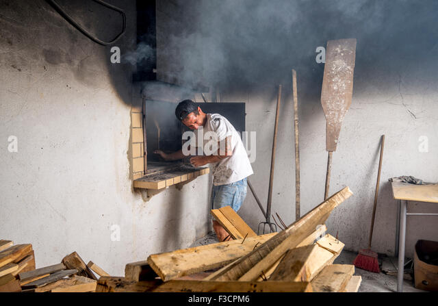 Young baker starting fire inside stone oven, causing lots of smoke. - Stock Image