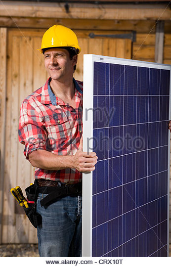 Engineer holding solar panel - Stock Image