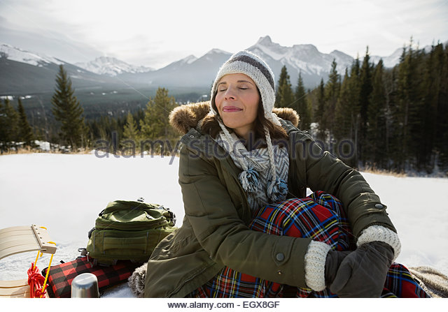 Woman in warm clothing enjoying mountain air - Stock Image