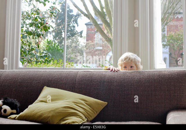 Portrait of cute male blond toddler hiding behind sofa - Stock Image