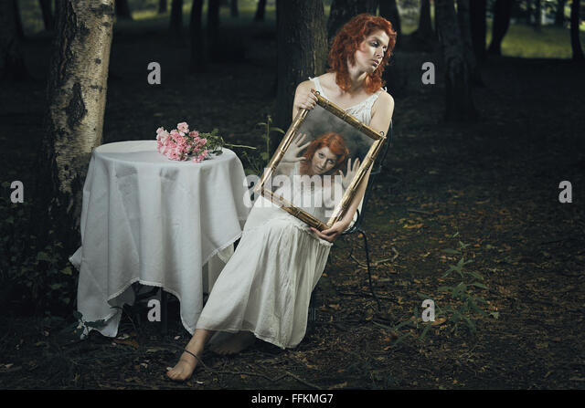 Soul of a woman trapped inside a mirror in a strange forest . Dark and surreal - Stock-Bilder