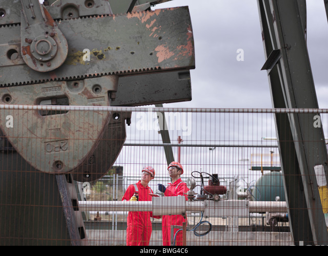 Workers looking up at oil well pump - Stock-Bilder
