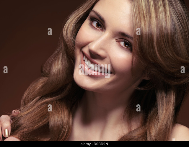 Beauty portrait of a smiling young woman with beautiful light brown hair - Stock Image