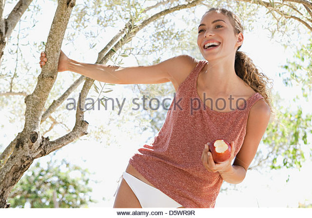 Smiling woman eating apple outdoors - Stock Image
