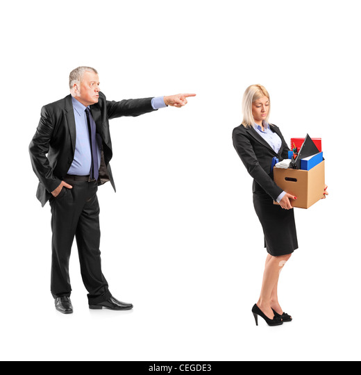 Full length portrait of an angry boss firing a woman in a suit carrying a box of personal items isolated on white - Stock Image