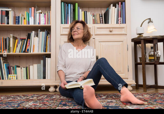 Senior woman sitting on the floor in front of bookshelf and reading, Munich, Bavaria, Germany - Stock-Bilder