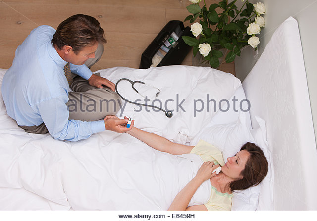 Doctor checking patientÂ's pulse on house call - Stock Image