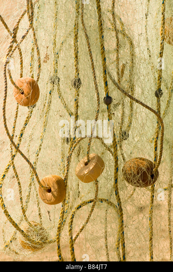 MEXICO SINOLA STATE MAZATLAN Colorful fishing net and buoys hanging from fishing boat to dry - Stock Image