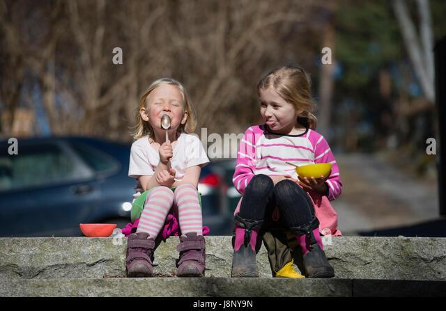 Girls (4-5) sitting on wall - Stock-Bilder