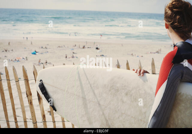 Surfer with surfboard on beach, Lacanau, France - Stock-Bilder