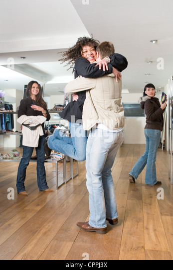 Woman joyfully hugging man in a clothes shop - Stock Image