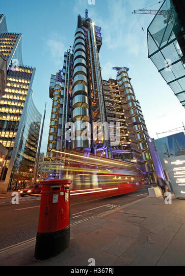 Red London bus passes Lloyd's building at dusk, Lime St, England - Stock Image