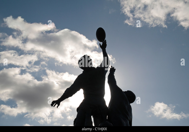 Back lit view of the bronze sculpture by Gerald Laing, depicting a rugby line-out, outside Twickenham Rugby Stadium, - Stock Image