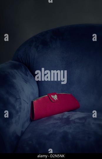 a red handbag lying on a blue armchair - Stock-Bilder
