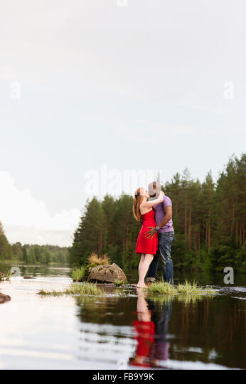 Sweden, Vastmanland, Bergslagen, Svartalven, Mid adult couple kissing - Stock Image